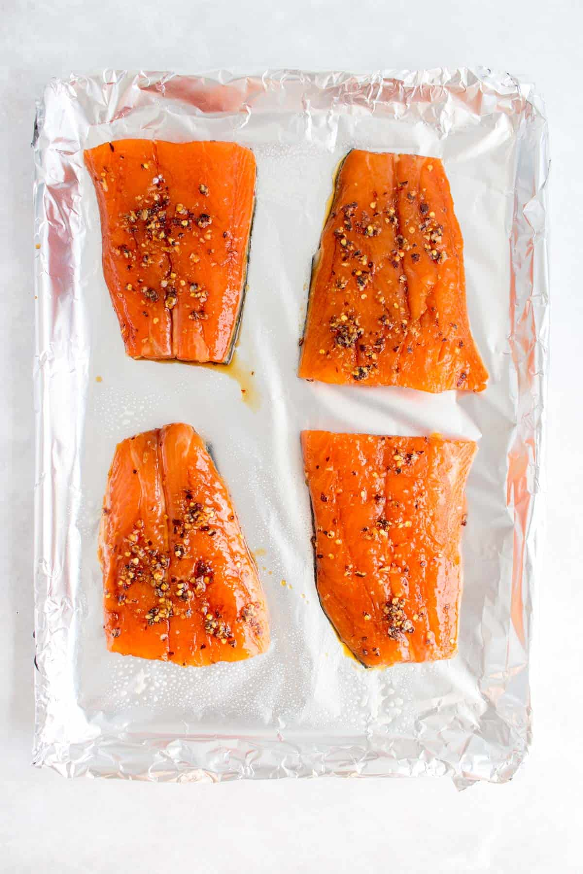 Four salmon fillets on a sheet pan.