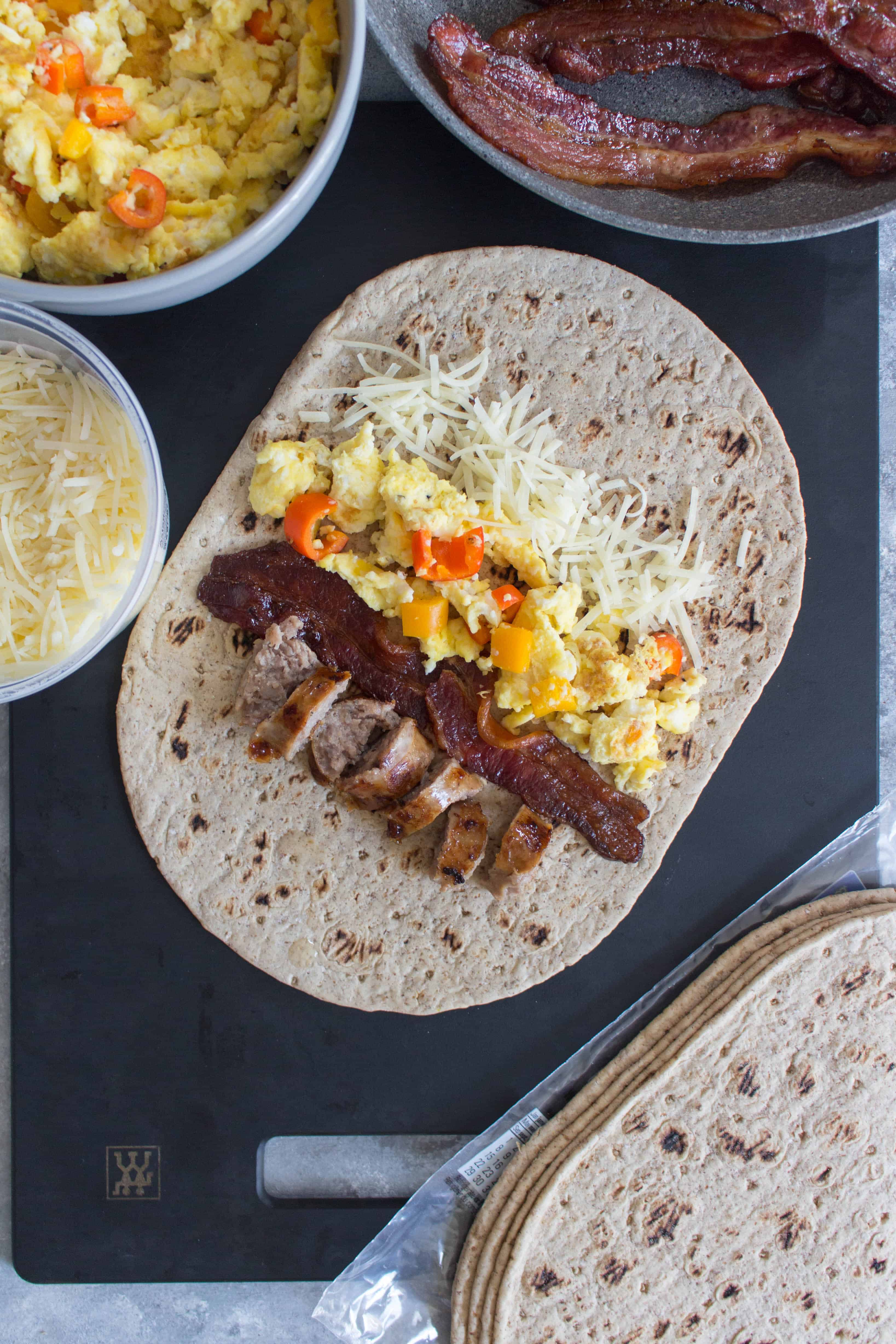 freezer friendly breakfast wraps laid down with ingredients (sausage, bacon, cheese, egg, bell peppers) shown
