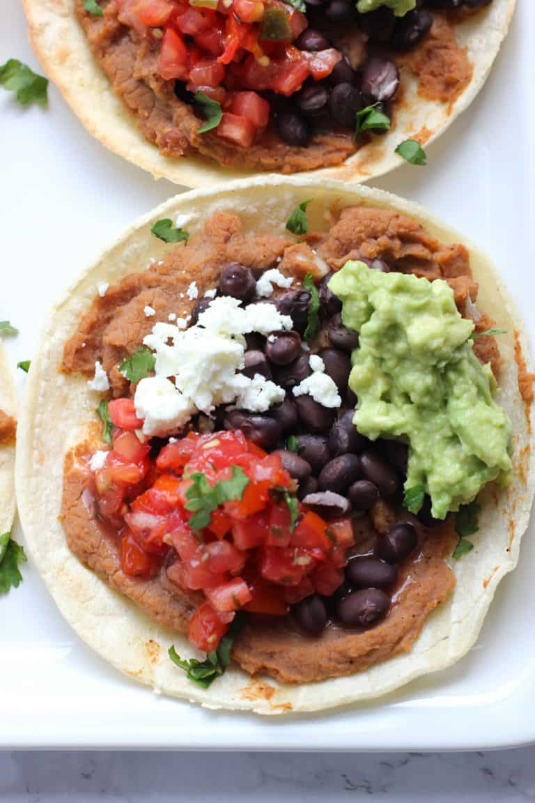 These oven baked tostadas heat up quickly which means you can have dinner on the table in just 15 minutes! They're vegetarian, gluten free, and customizable for the whole family!
