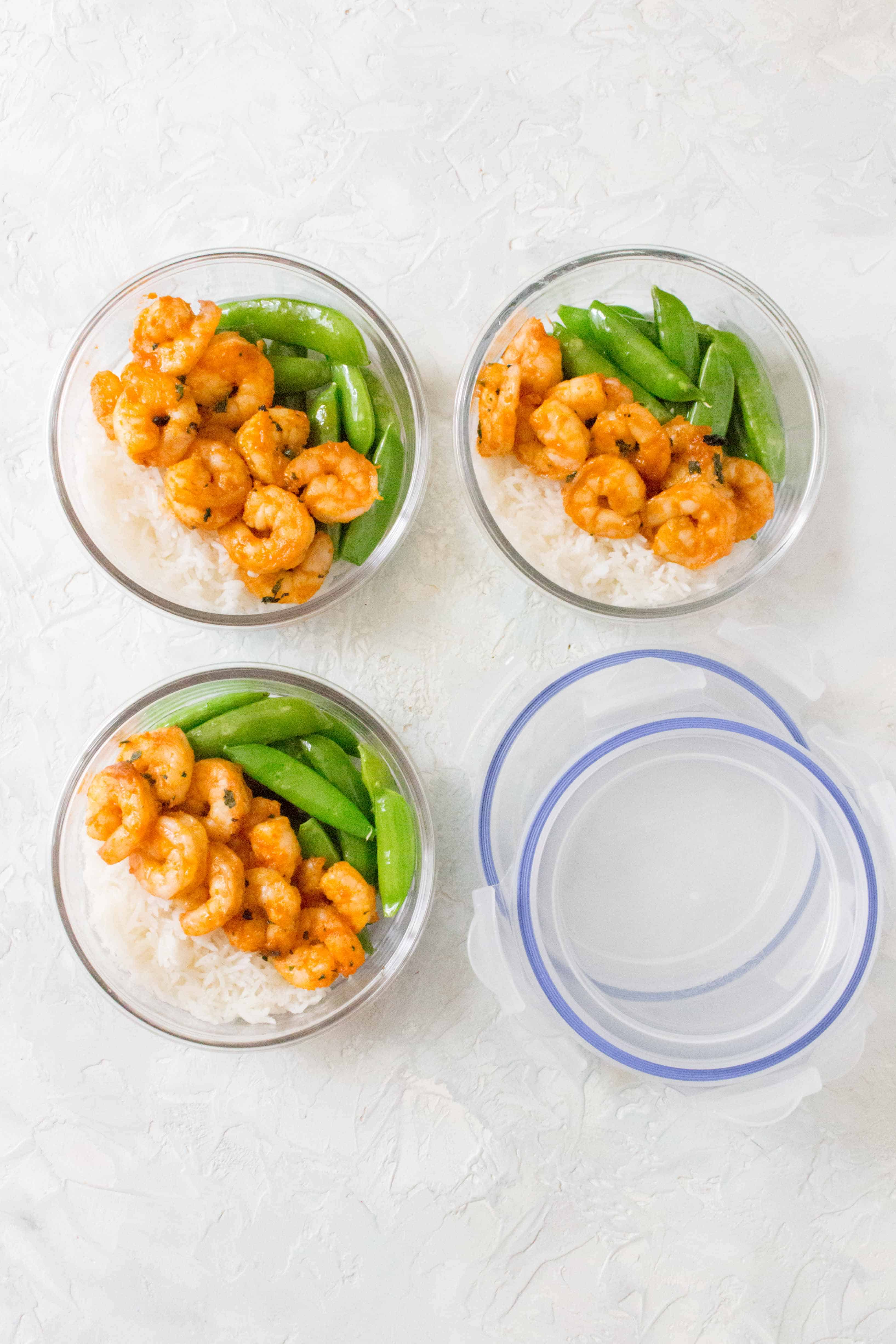 Three round containers with rice, shrimp, and snap peas.