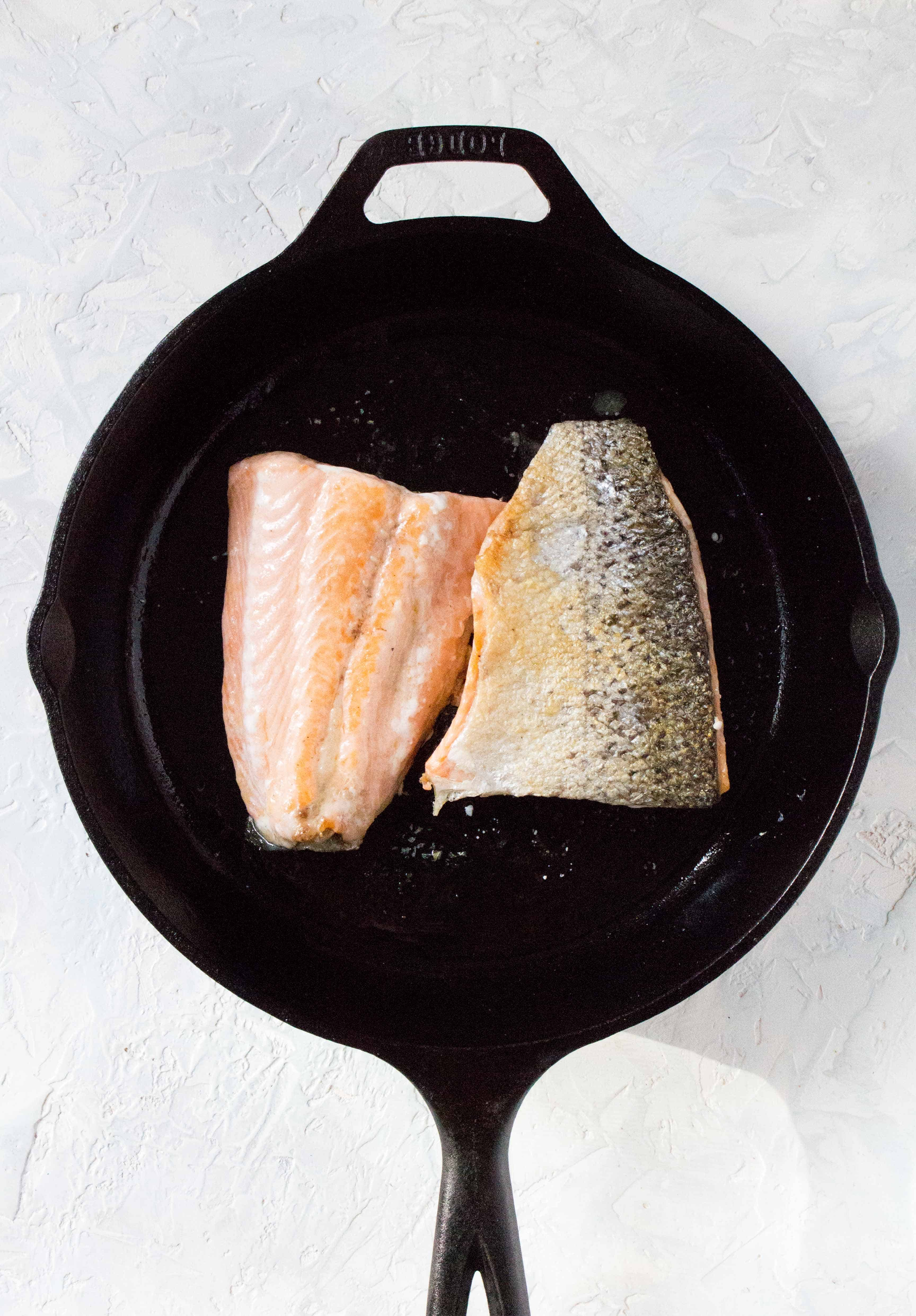 A cast iron with two salmon fillets.