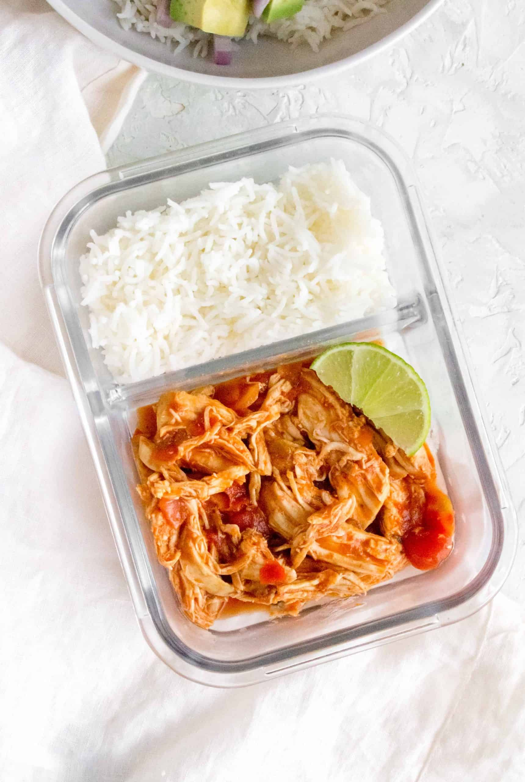 saucy shredded chicken in a glass meal prep container with some rice