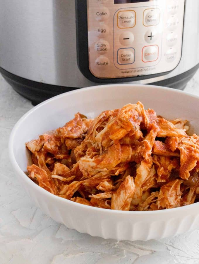 bowl of shredded salsa chicken in front of the Instant Pot