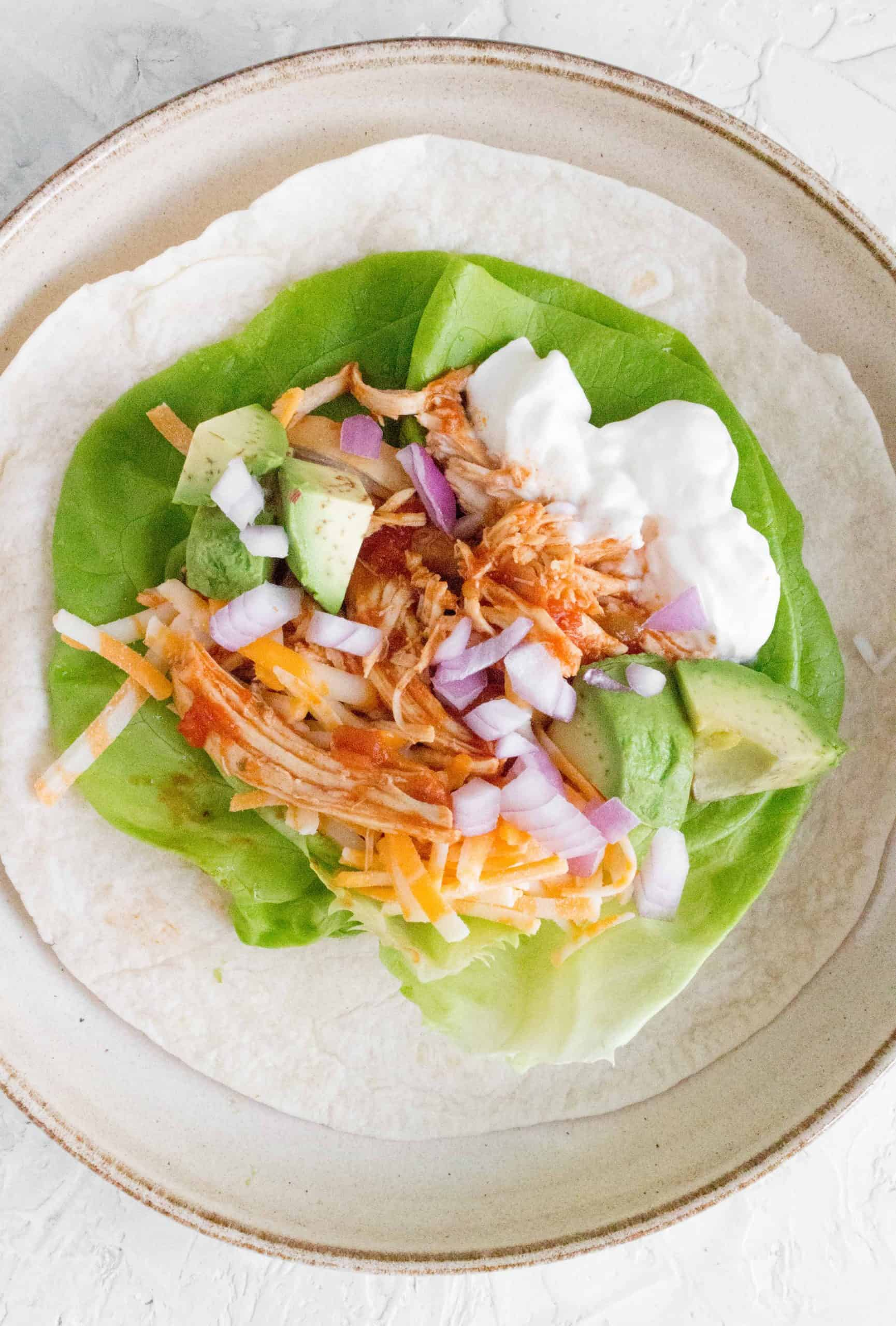 shredded chicken on top of lettuce and tortilla as an open faced taco