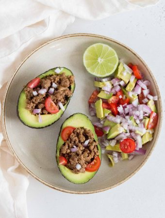 Tacos... but with an avocado. It's hard to go wrong with this switcharoo! Load up the halved avocados with the easiest taco meat and toppings of your choice for an easy dinner tonight!
