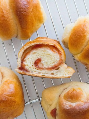 Here's how you can make strawberry swirled, fluffy, pillowy soft Hokkaido style milk bread rolls at home with this simple recipe. The perfect make ahead bread as they stay soft for days! Try these Japanese Milk Bread Rolls tonight!