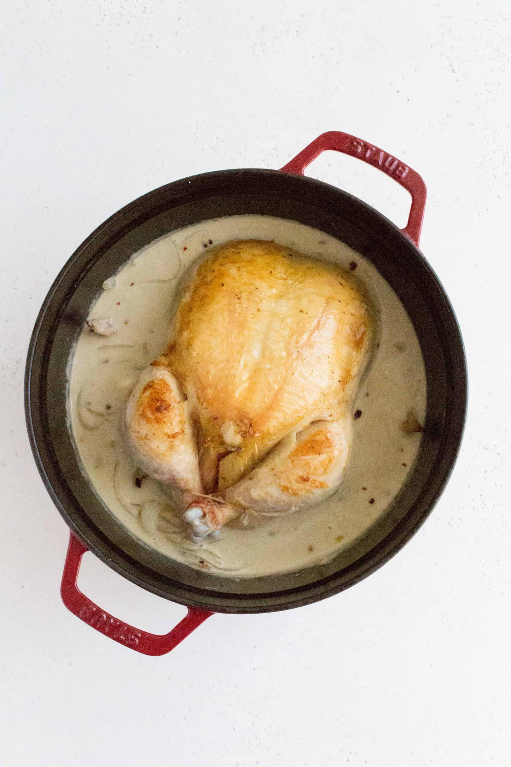 Set aside the chicken and in the pot, add onions, garlic, and crushed red pepper flakes. Sauté until the onions have softened. Add in the coconut milk and green curry paste and bring it to a boil. Add the chicken back in, breast side up, cover, and simmer on medium for 35-40 minutes.