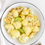 Plate with roasted cauliflower with 2 wedges of lime and a bit of parmesan on top