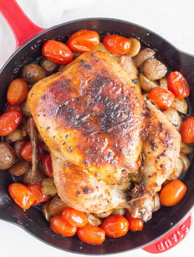 whole roast chicken in a cast iron staub skillet with baby potatoes and grape tomatoes