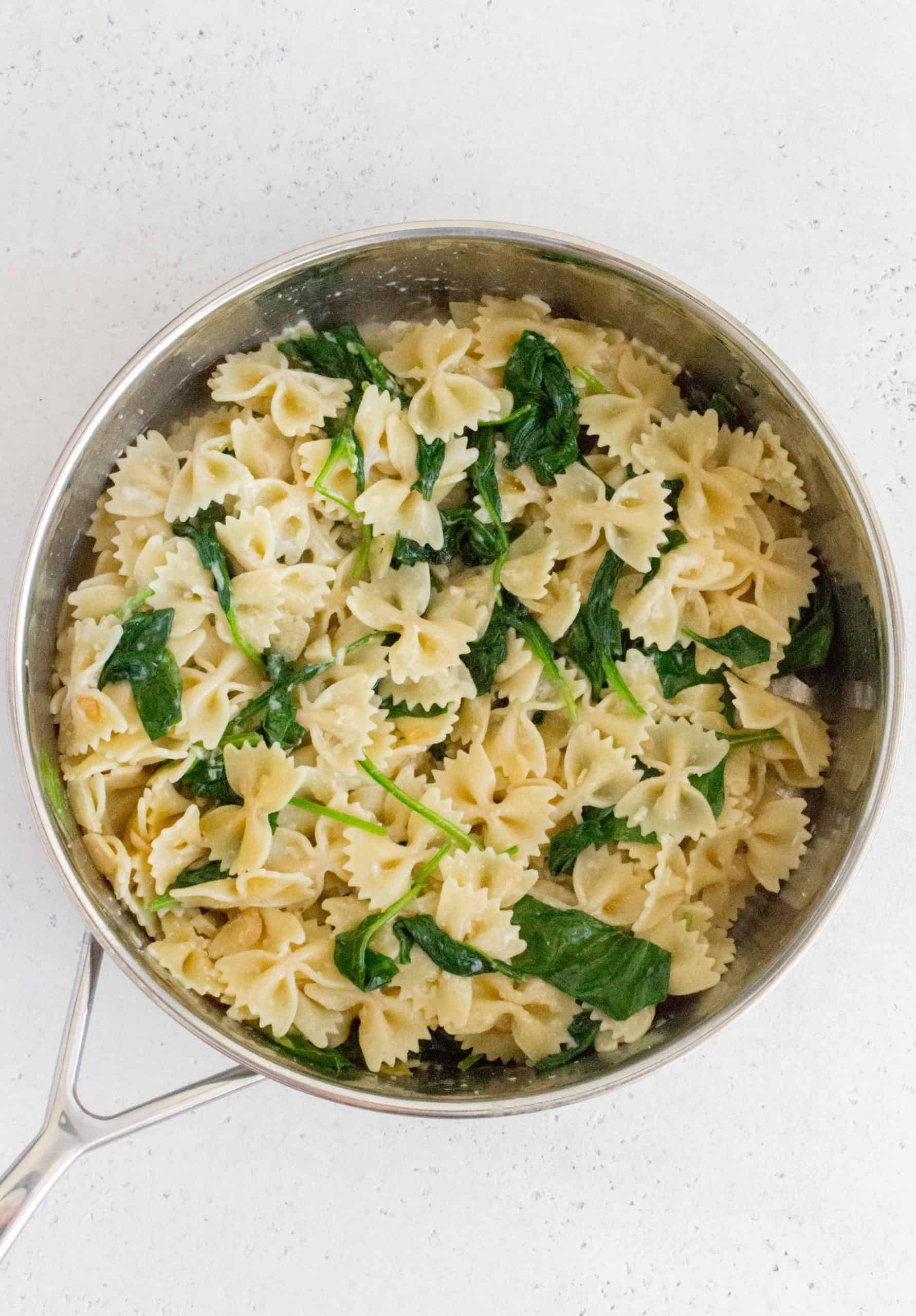 saute pan with bow tie pasta and spinach, wilted