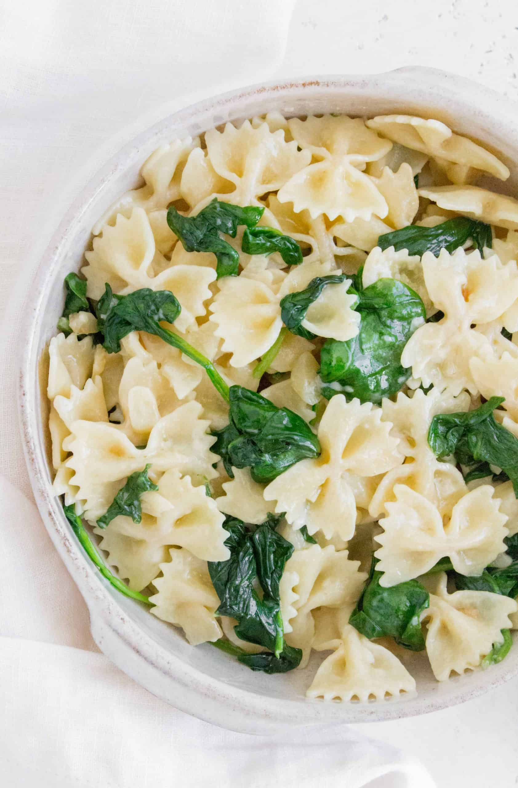 bowl with bow tie pasta with garlic and spinach with a butter sauce