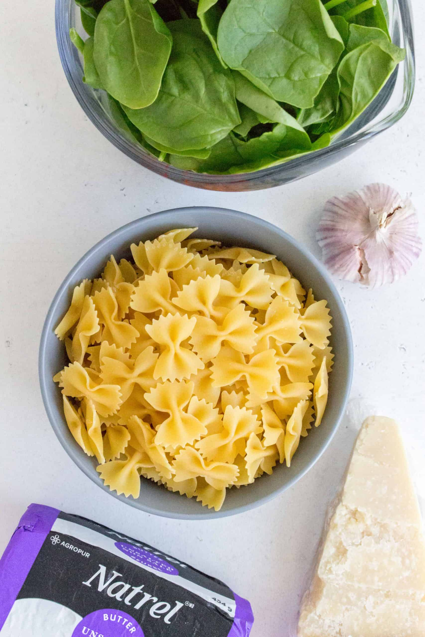 ingredients for butter pasta: bow tie pasta in a blue bowl, butter, spinach, parmesan, and garlic