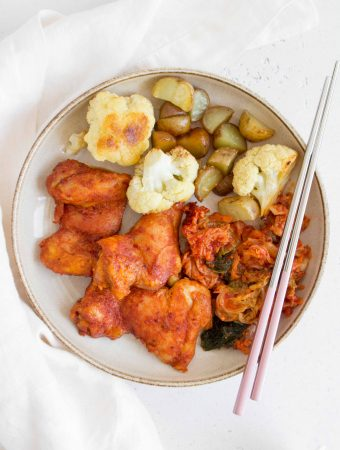 plate with spicy korean chicken thighs, roasted cauliflower, mini potatoes, and kimchi