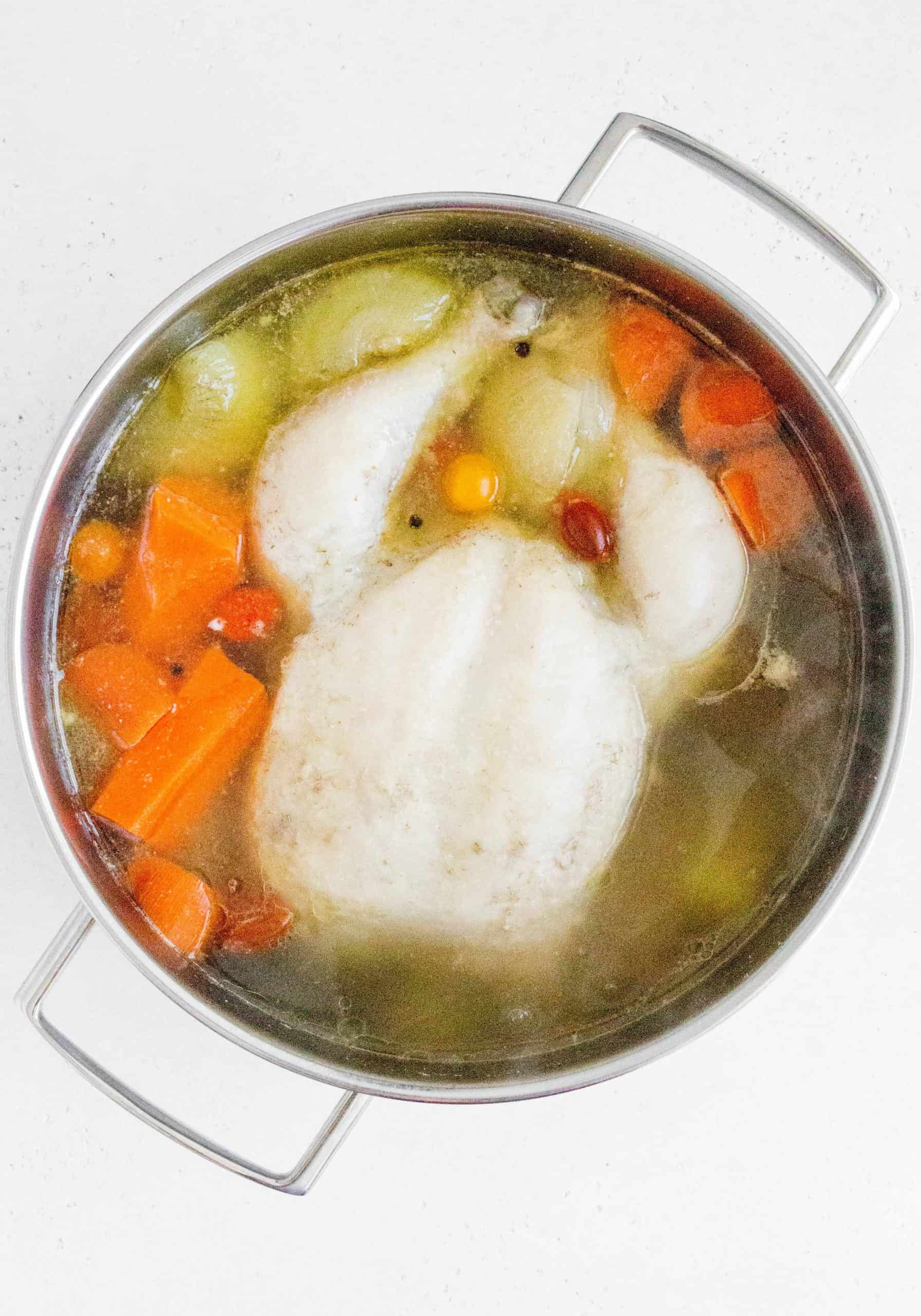 Chicken inside of a stock pot with broth inside.