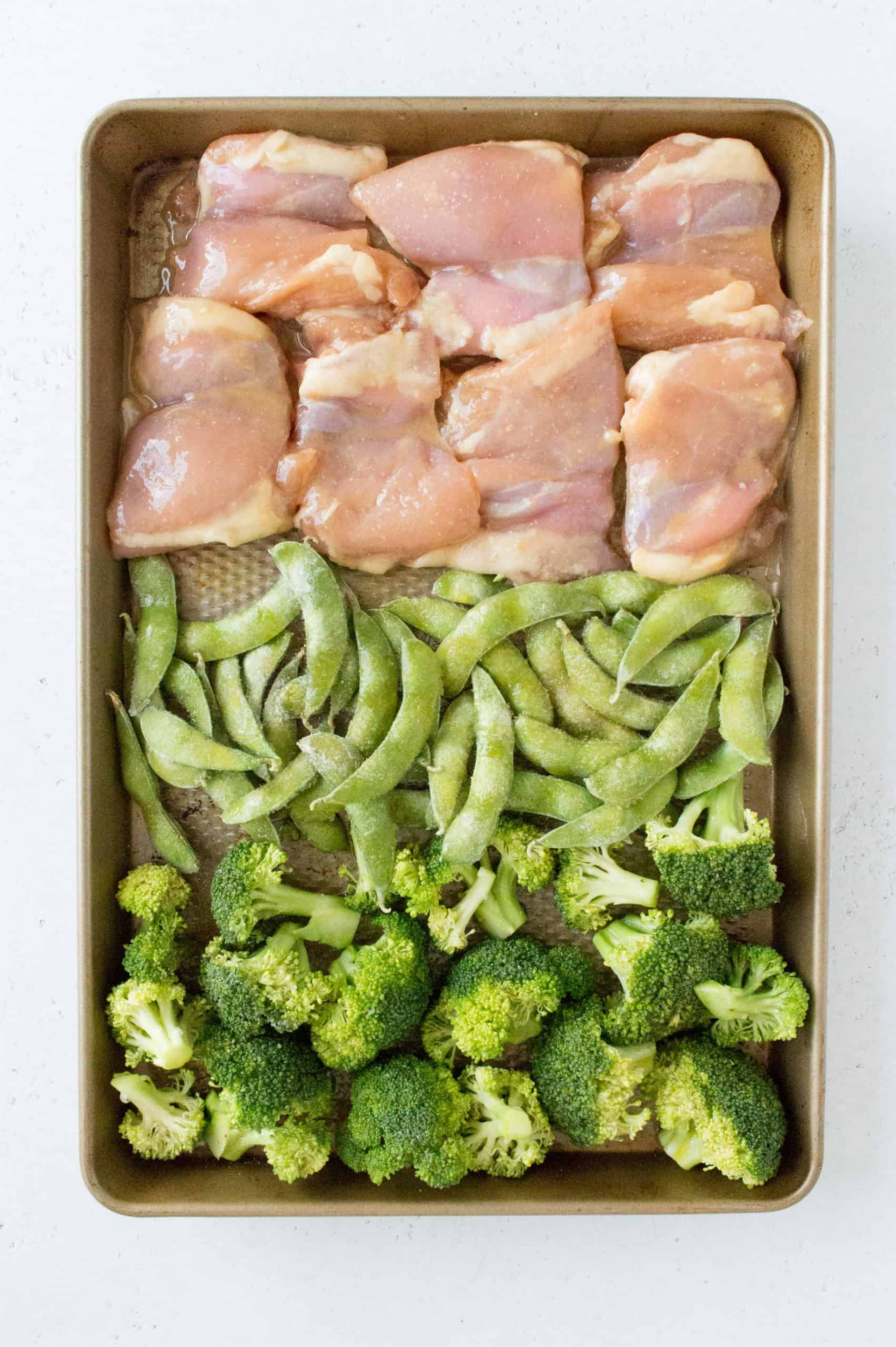 sheet pan miso chicken with broccoli and edamame before roasting in oven in a sheet pan