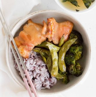 miso baked chicken thighs in a bowl with broccoli edamame and purple rice