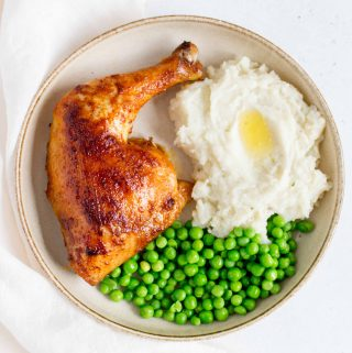 plate with a oven roasted chicken quarter with mashed potatoes and peas