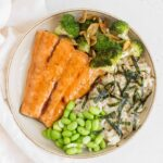 plate with teriyaki salmon with broccoli, edamame, brown rice, and seaweed