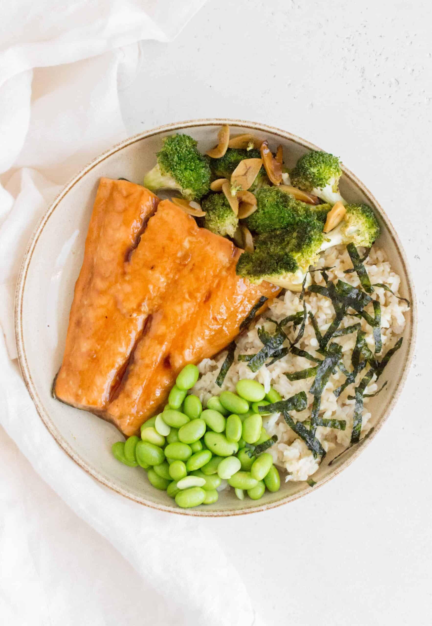 plate with teriyaki salmon with broccoli, edamame, brown rice, and seaweed