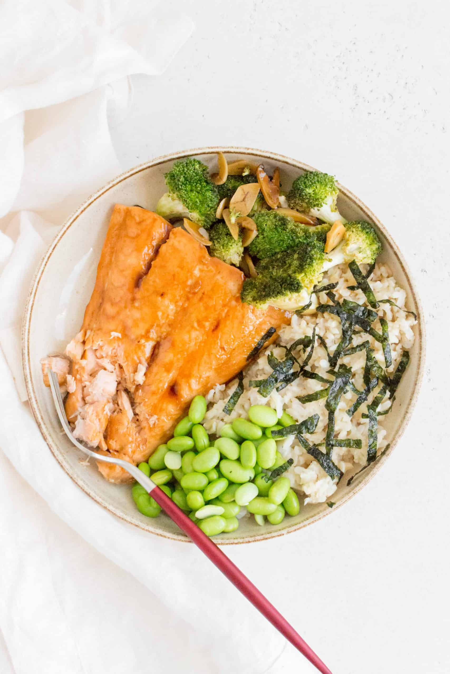 plate with teriyaki salmon broken up by a fork with broccoli, edamame, brown rice, and seaweed