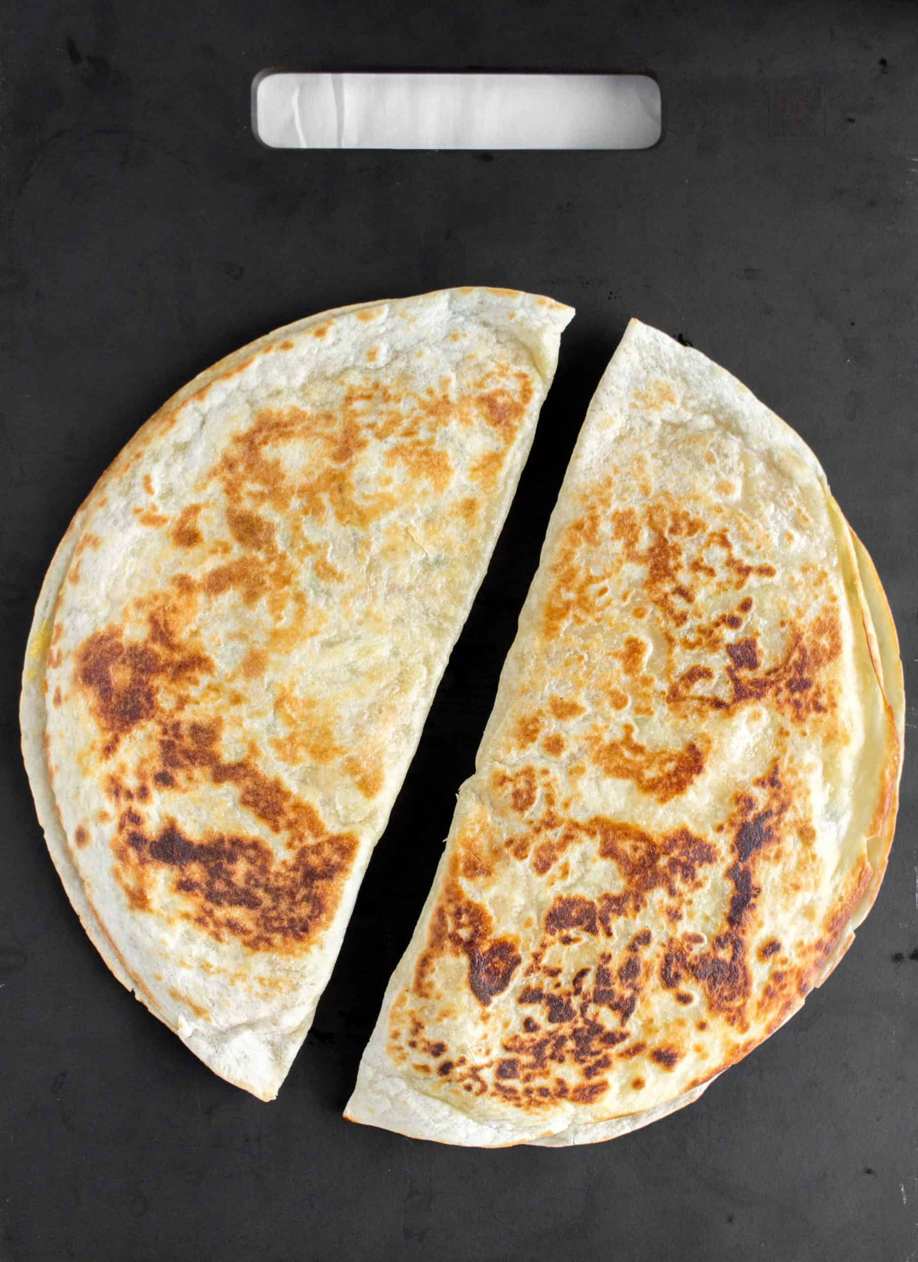 Two chicken and hummus quesadillas on a black surface.