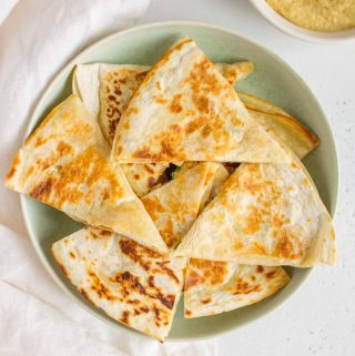 green plate with chicken and hummus quesadillas