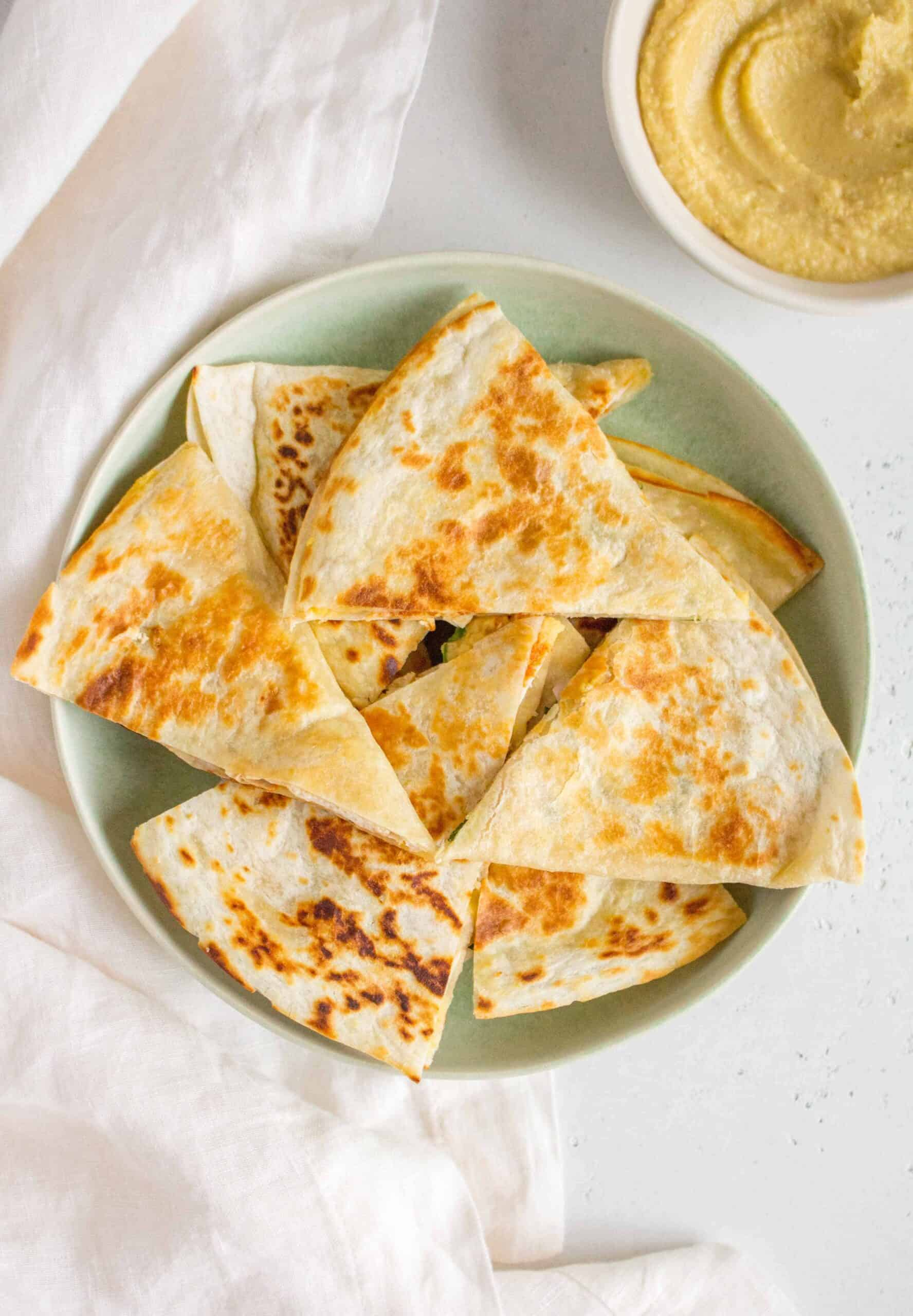 green plate with chicken and hummus quesadillas.