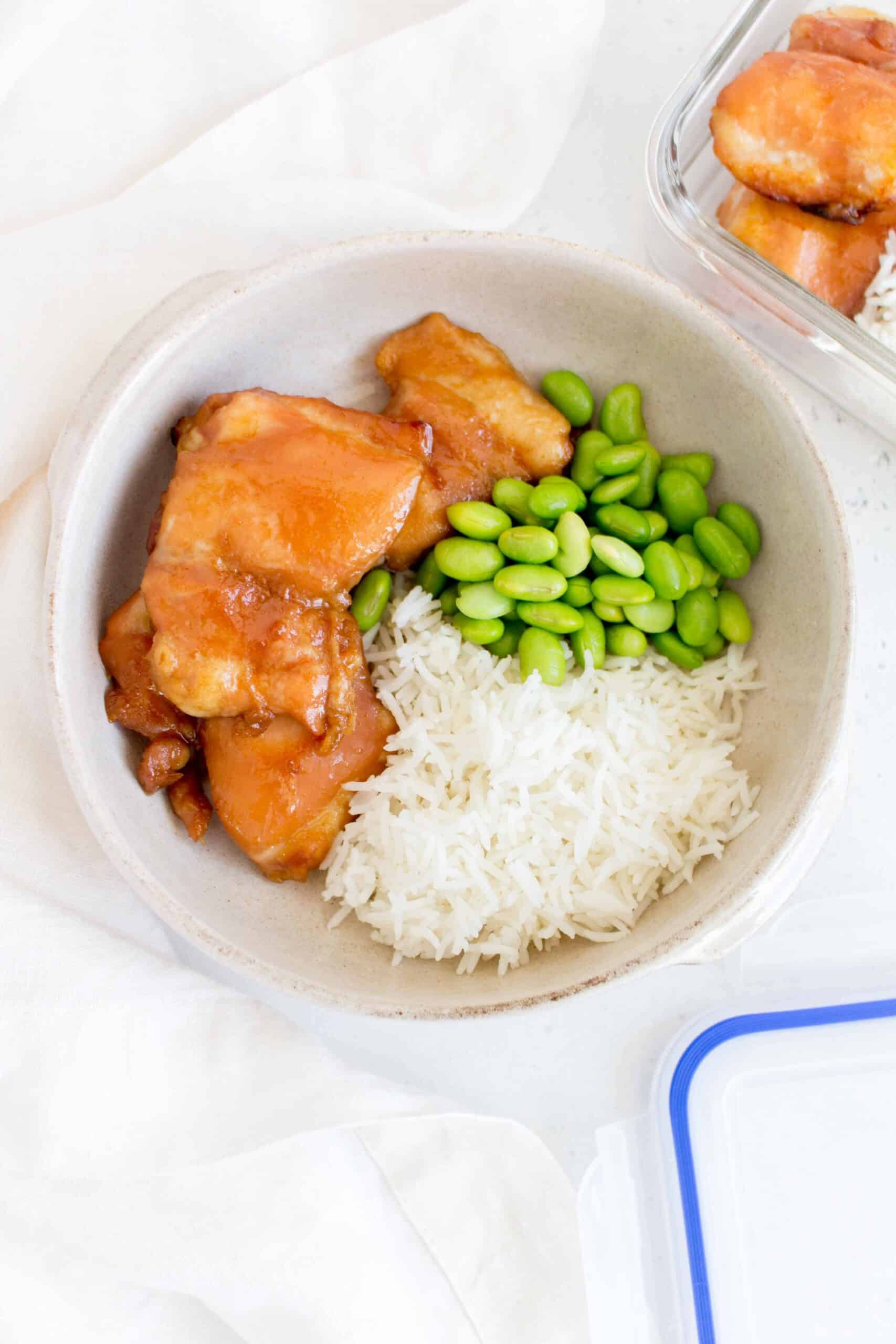 plate with honey soy chicken thighs along with a serving of rice and edamame beans