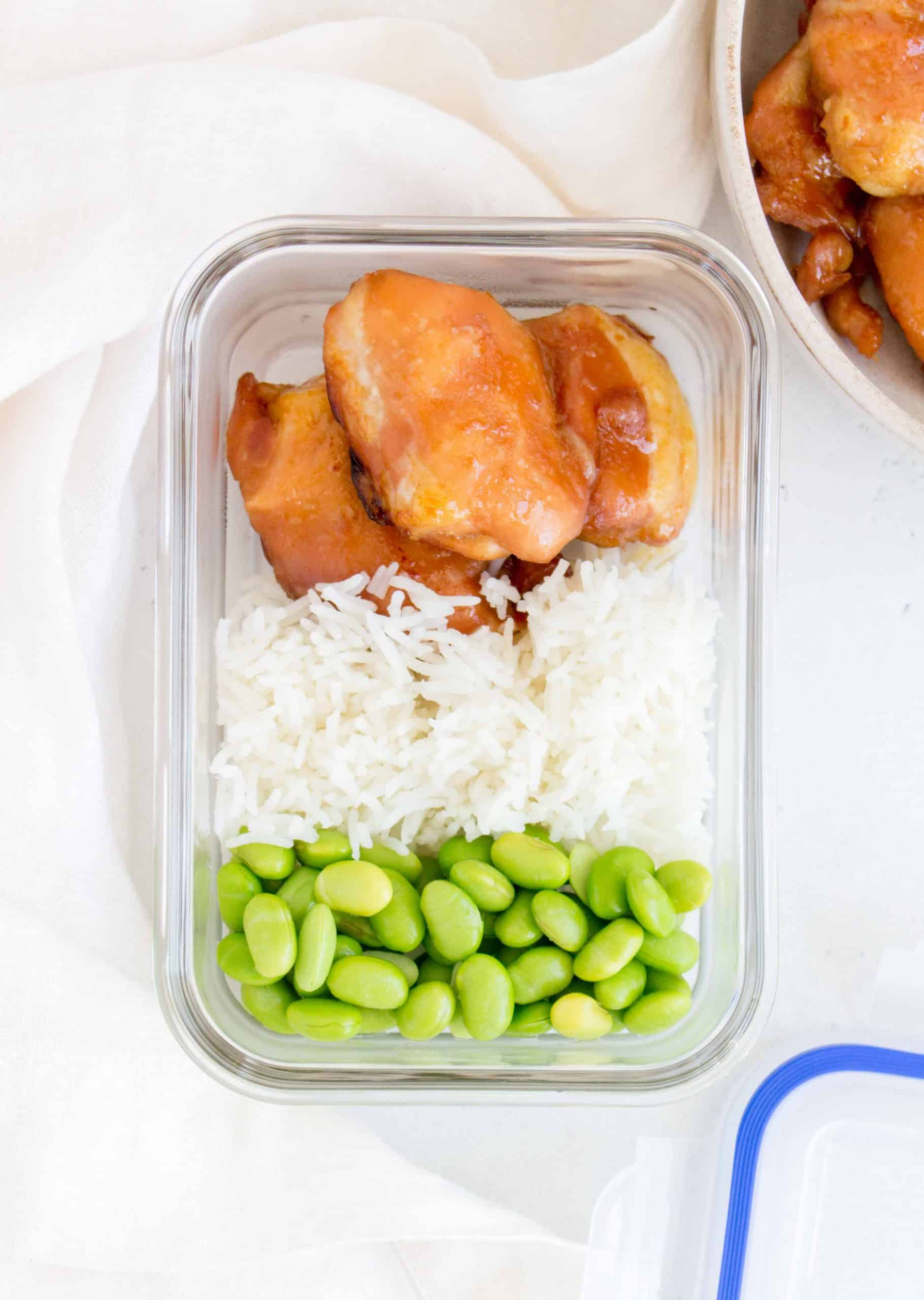meal prep container containing honey soy chicken thighs, rice, and edamame beans