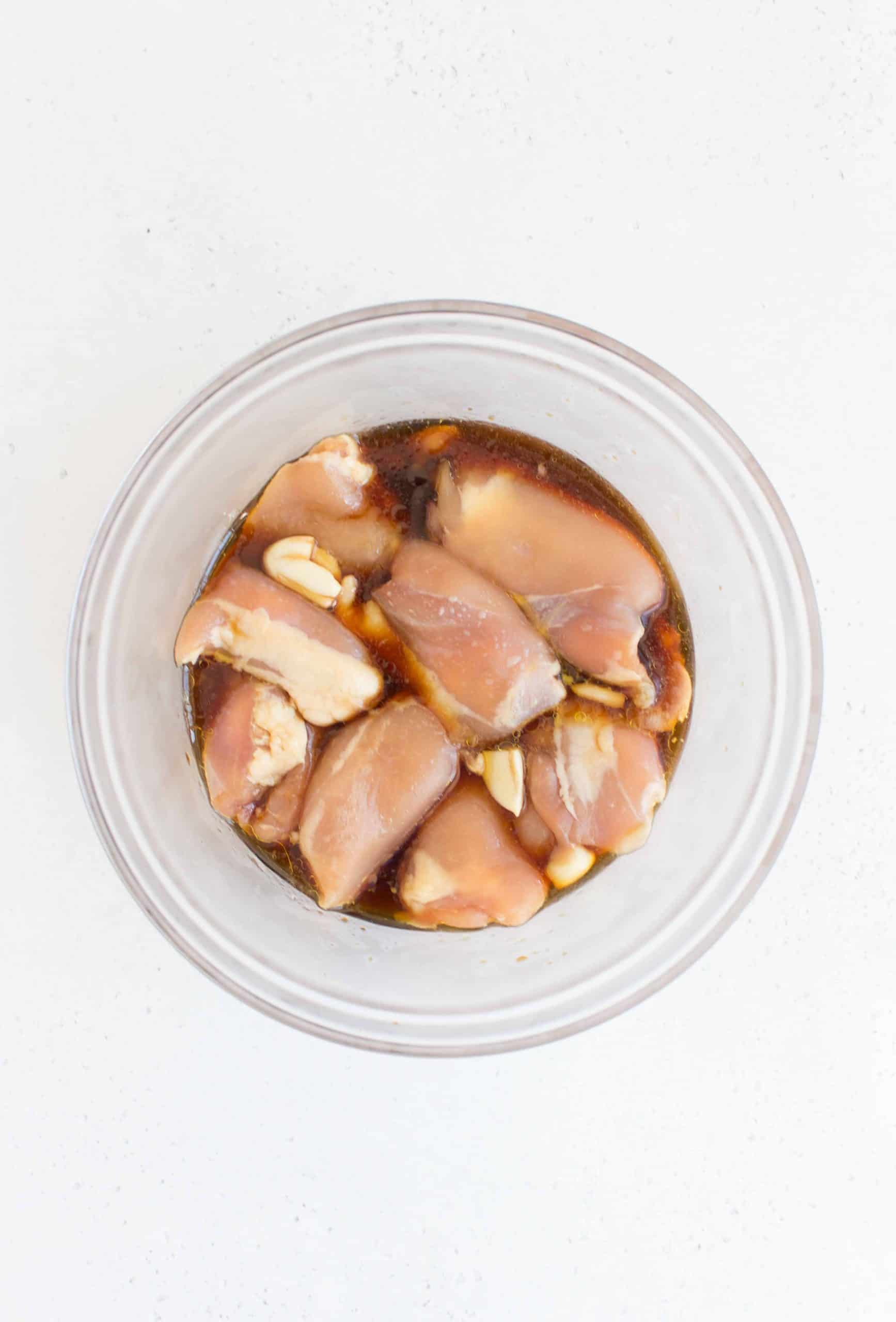 glass bowl marinating chicken thighs