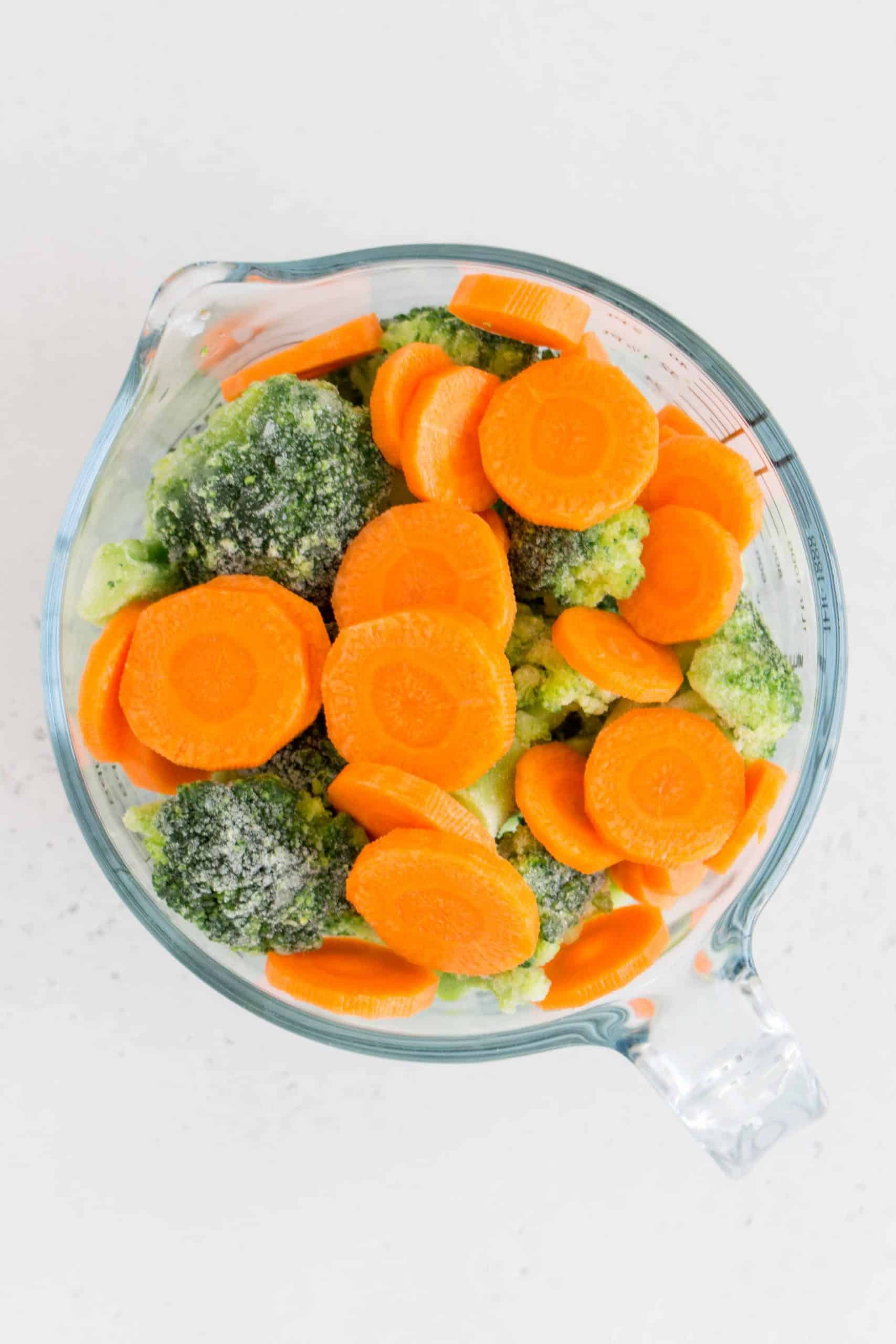 broccoli florets and carrots in a measuring cup.