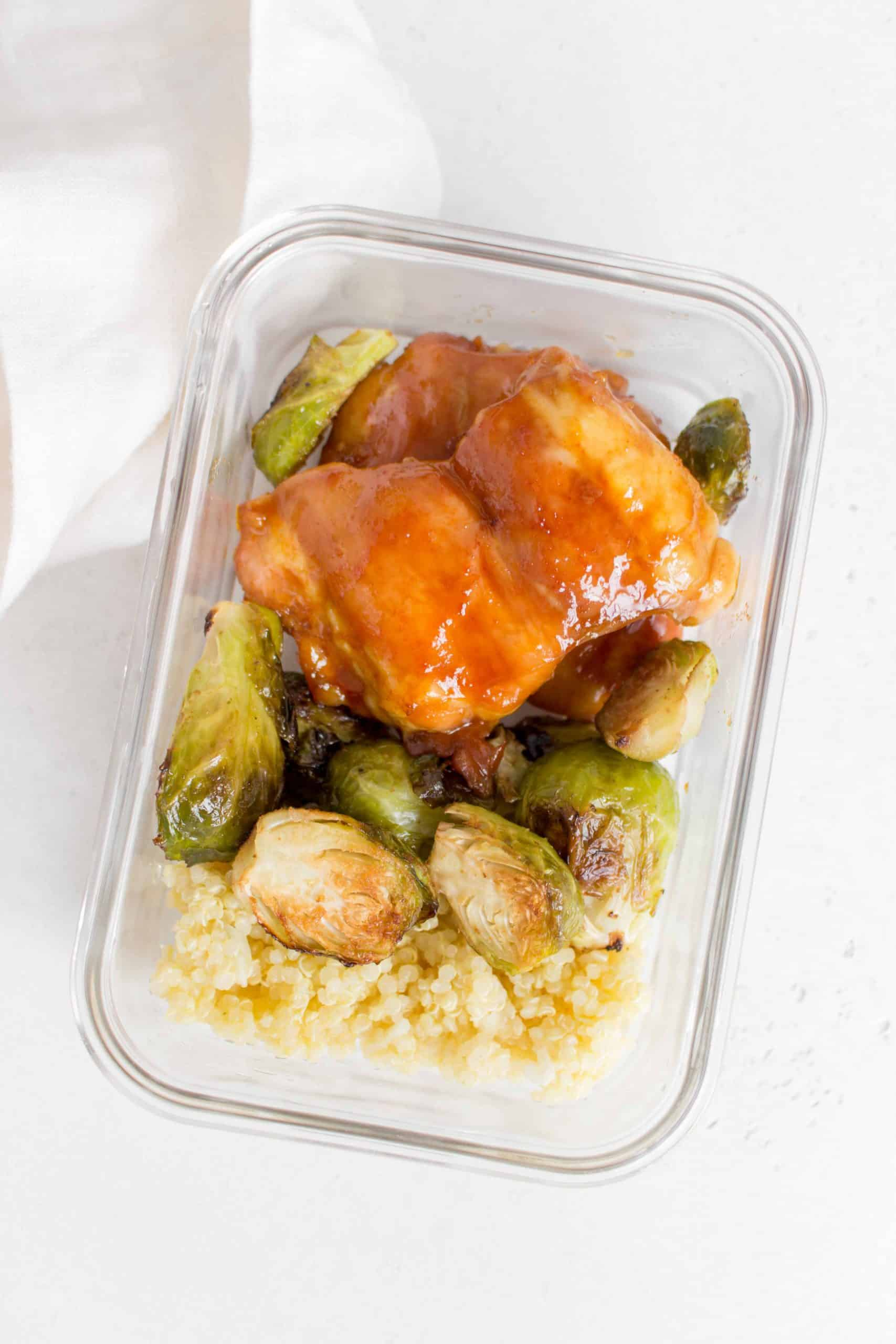 chicken thighs in meal prep container with brussels sprouts and quinoa