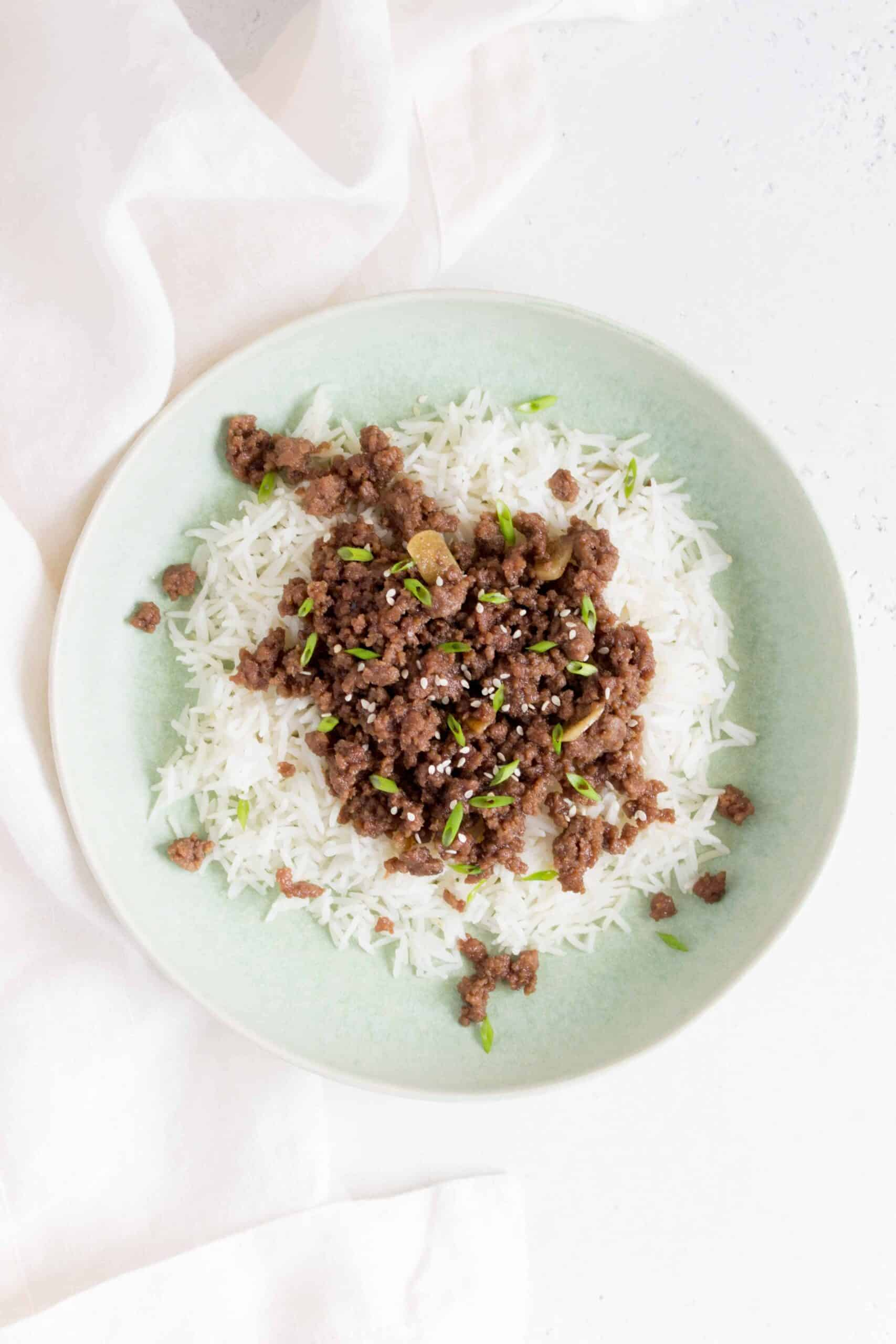 A green bowl with rice and teriyaki beef.