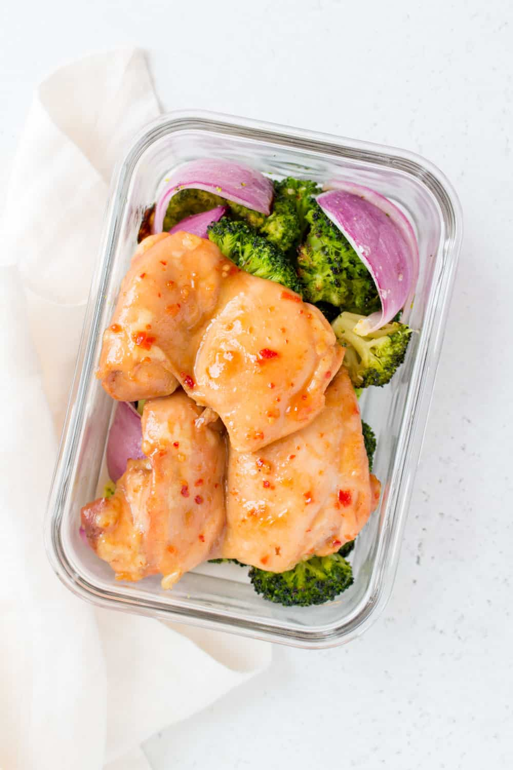 meal prep container with roasted broccoli, red onion, and oven baked chicken thighs with honey chili sauce