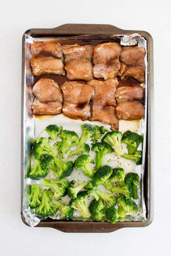 honey black pepper chicken with broccoli in a sheet pan before baking