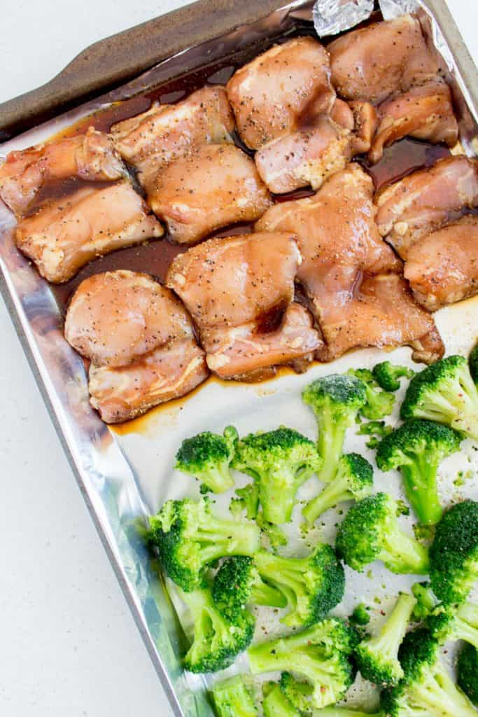 close up of honey black pepper chicken with broccoli in a sheet pan before baking