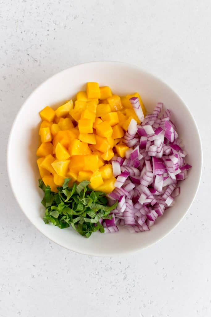 bowl of mango salsa ingredients: mango, red onion, and basil