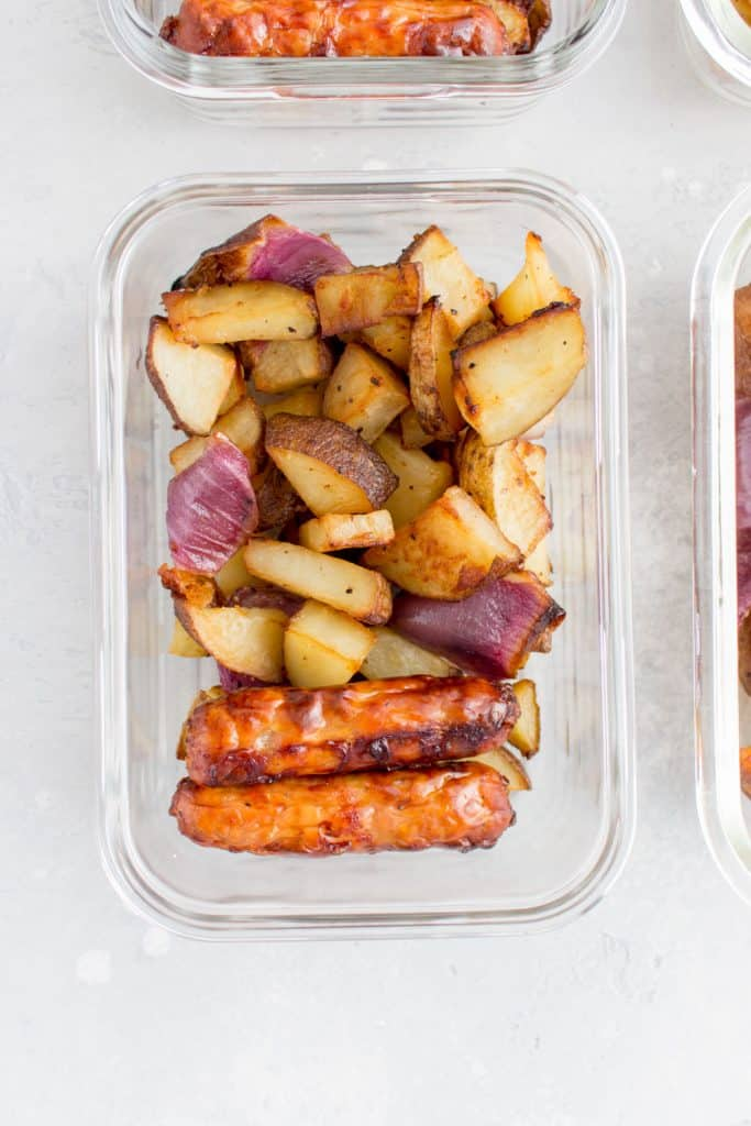 glass container with pork breakfast sausages and roasted potatoes with red onions
