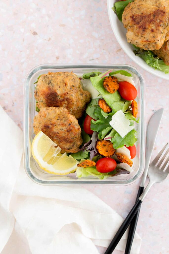 chicken patties with a side of salad in a meal prep container