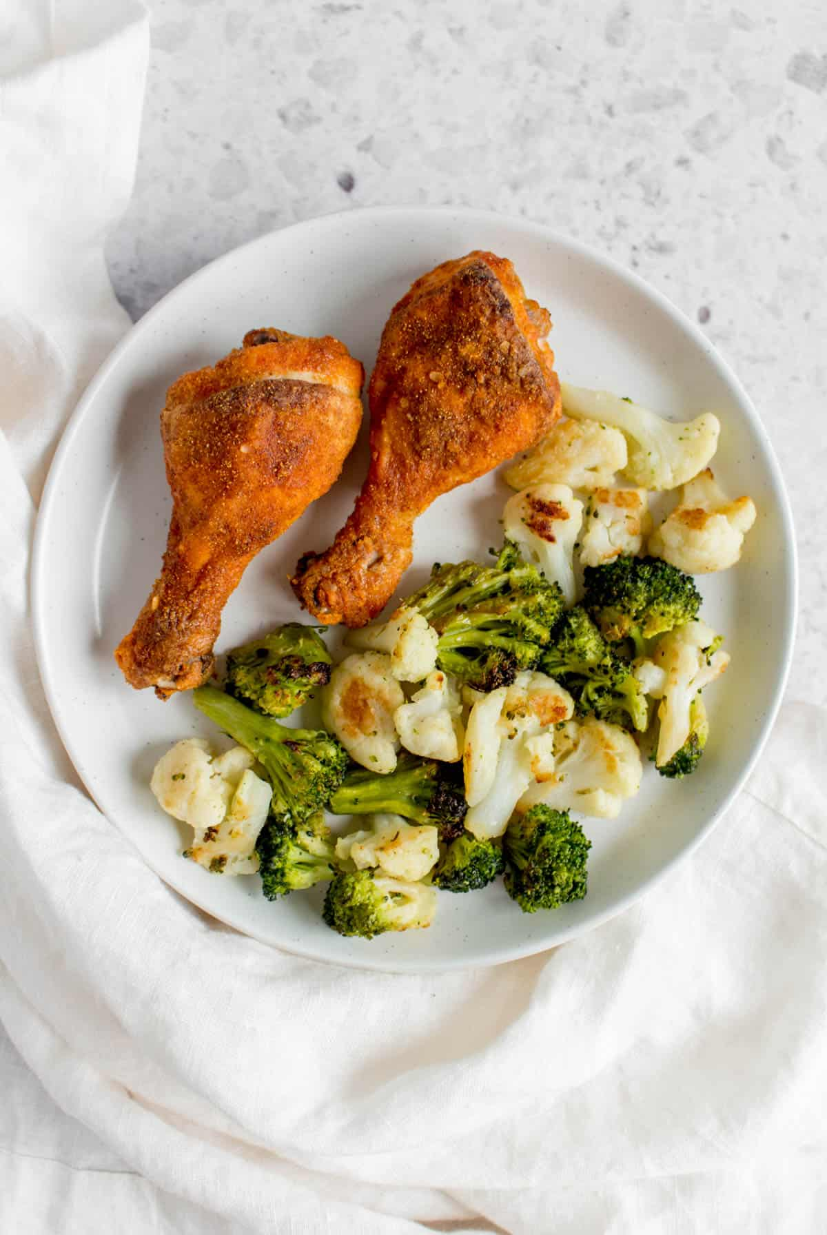 two crispy baked drumsticks on a white plate with broccoli and cauliflower