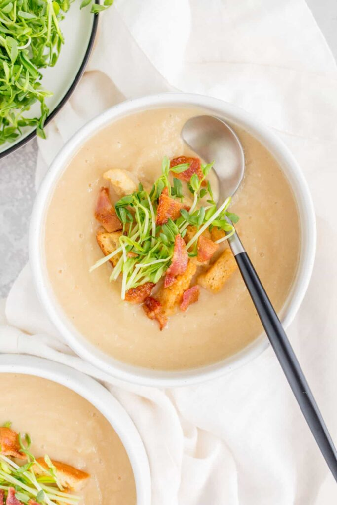 bowl of parsnip soup with spoon in it