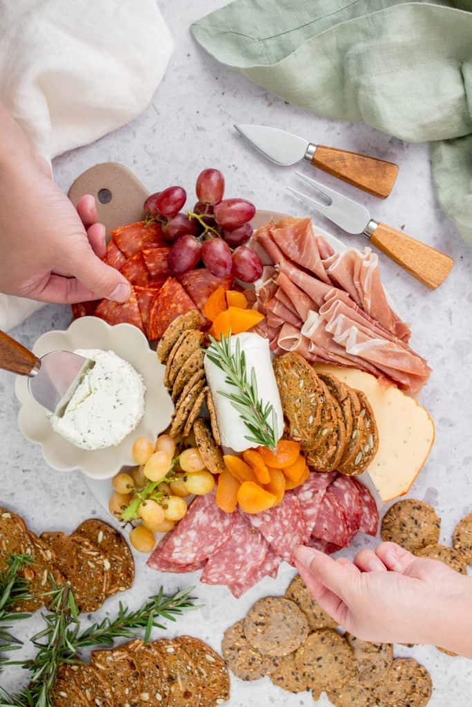 hands grabbing meat on charcuterie board