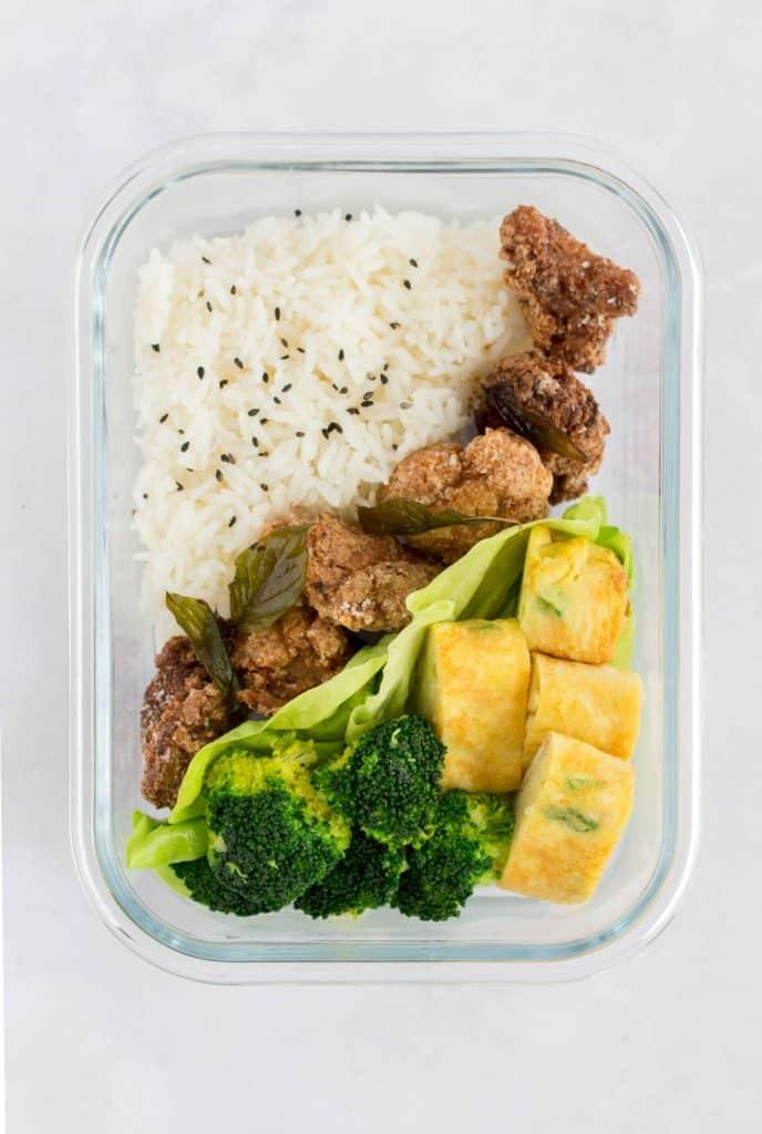 Bento box with rice, popcorn chicken, broccoli, and egg.