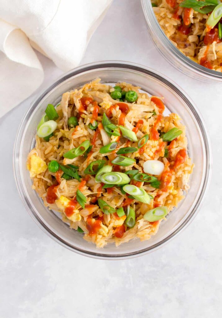 Round glass meal prep container with sriracha fried rice inside with green onions and hot sauce drizzled on top.