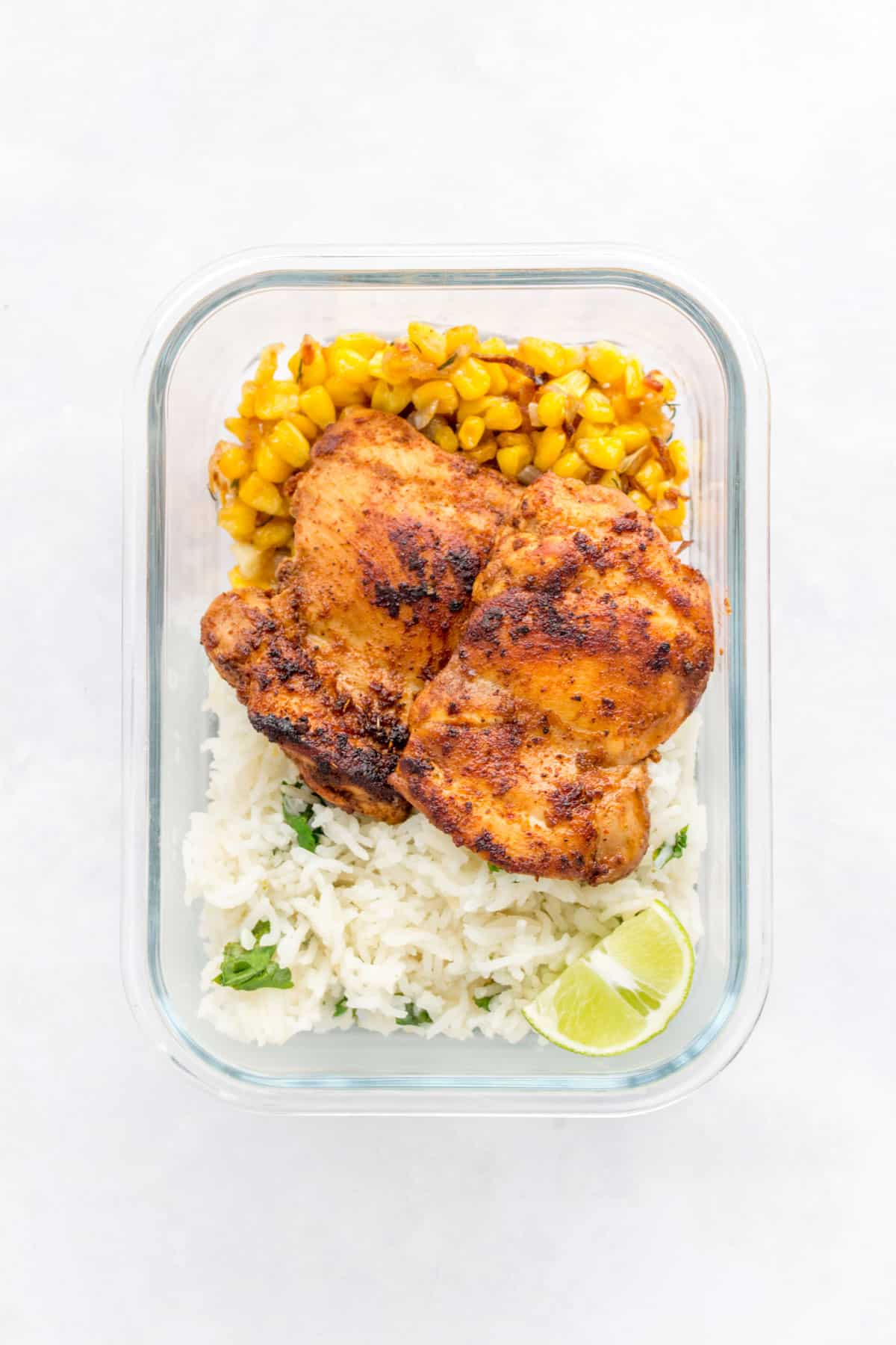 A glass meal prep container with chipotle chicken, caramelized corn, and cilantro lime rice.