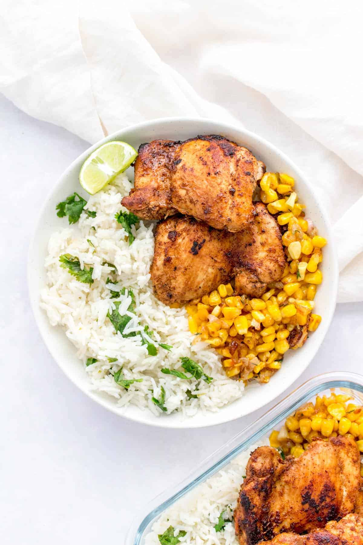 A white plate with chipotle chicken, caramelized corn, and cilantro lime rice.