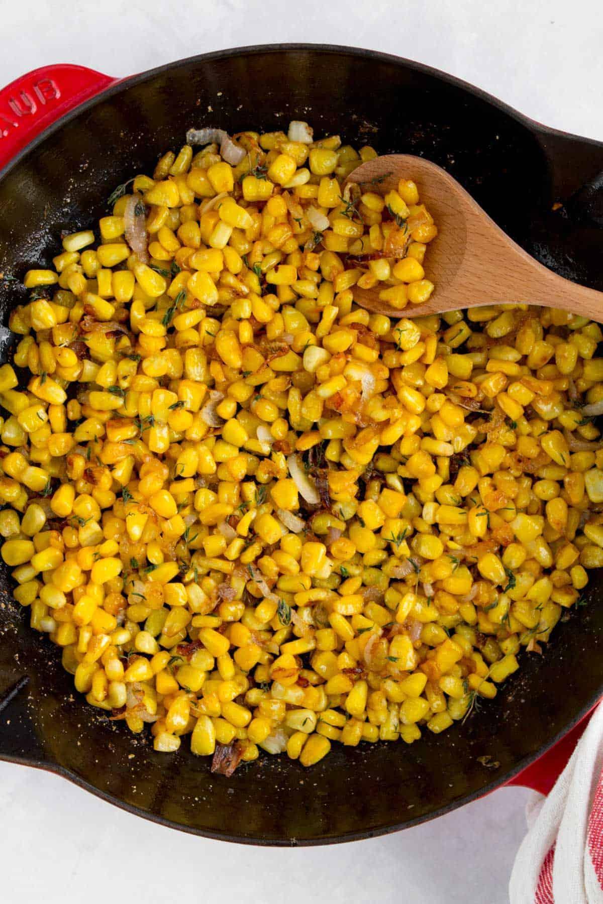 Close up of caramelized corn with shallots in a staub frying pan.