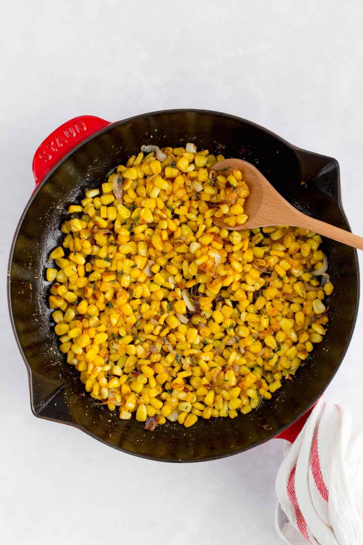Caramelized corn with shallots in a staub frying pan.