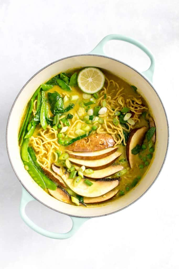 Curry ramen garnished with lime and green onions.