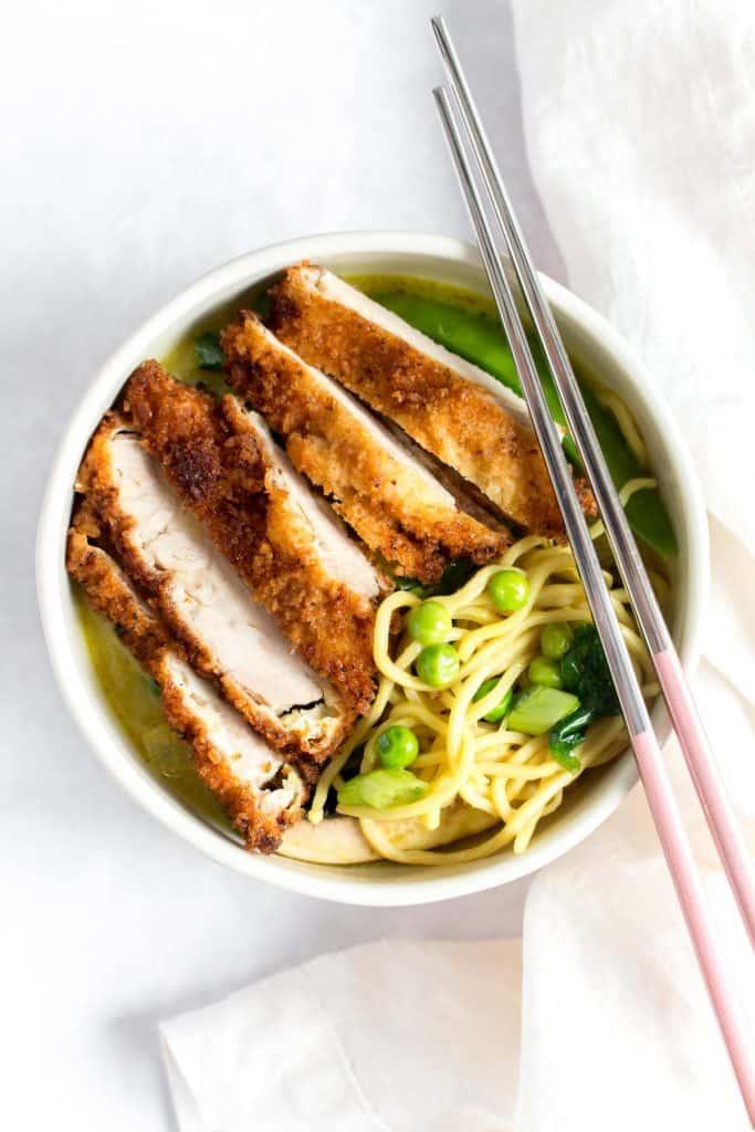 Chicken katsu in a bowl of curry ramen.